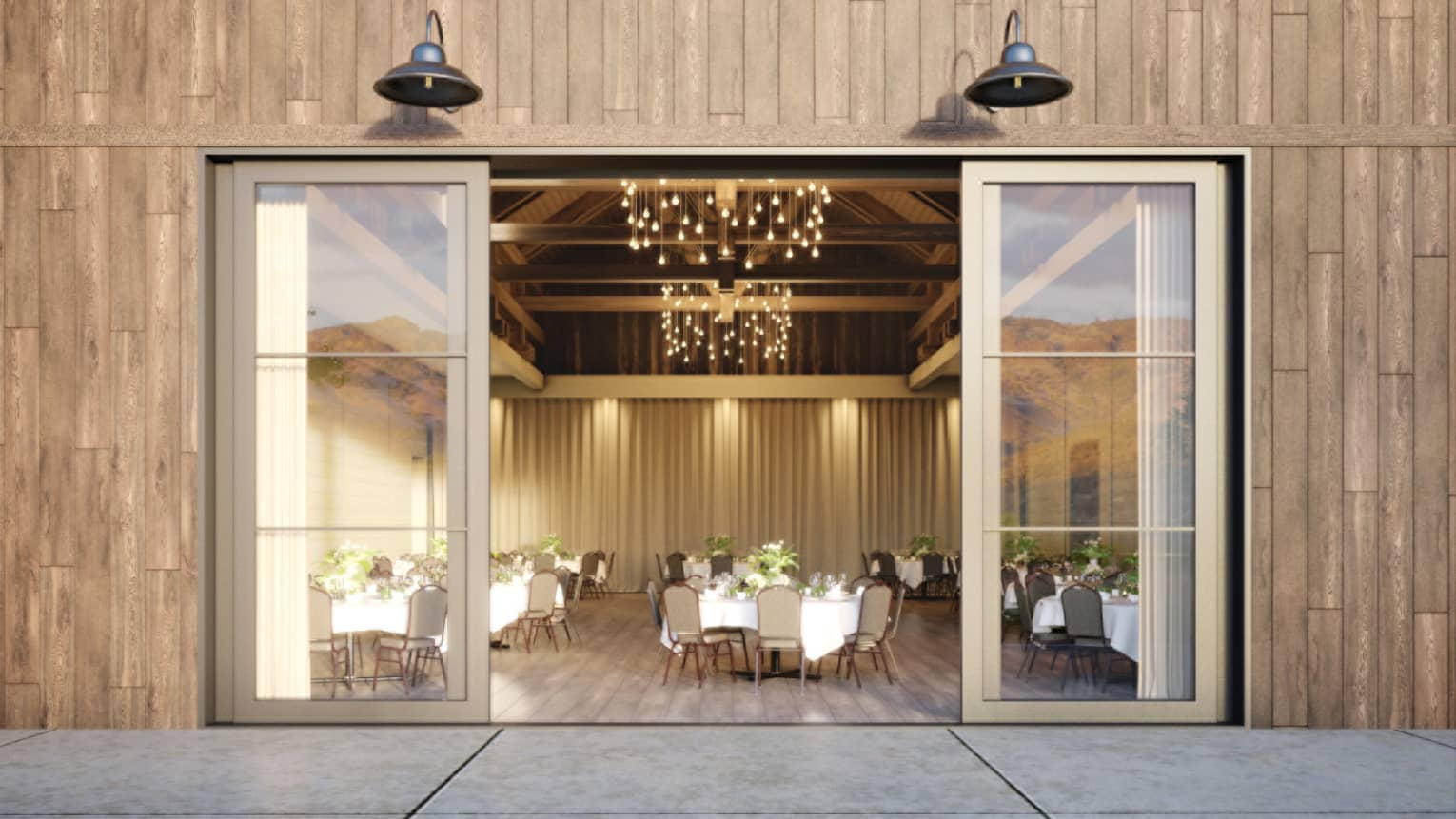 View from patio through large sliding glass doors to elegant event space with tables, chandelier