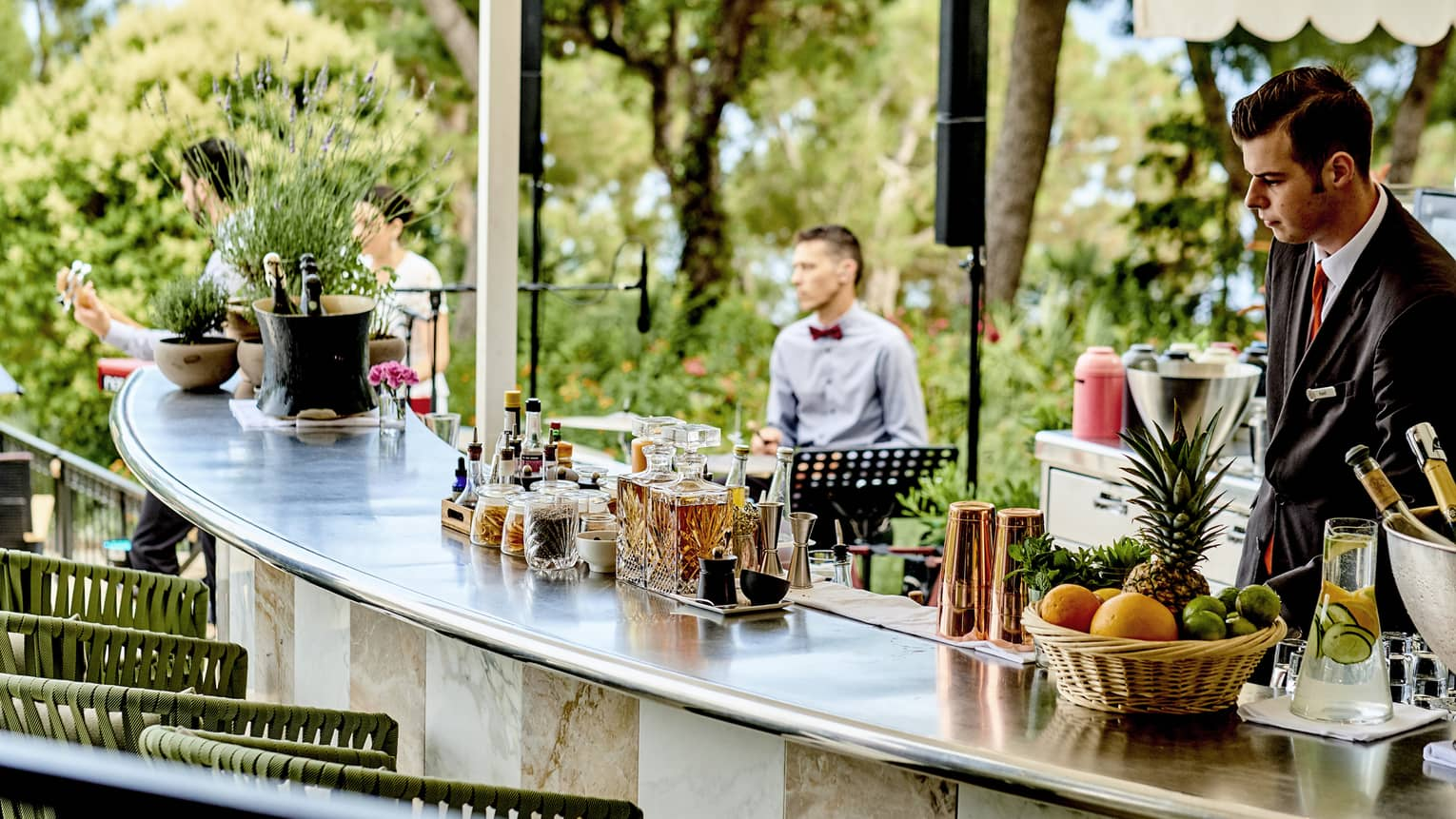 Bartender, staff behind large curved bar with drinks in garden lounge