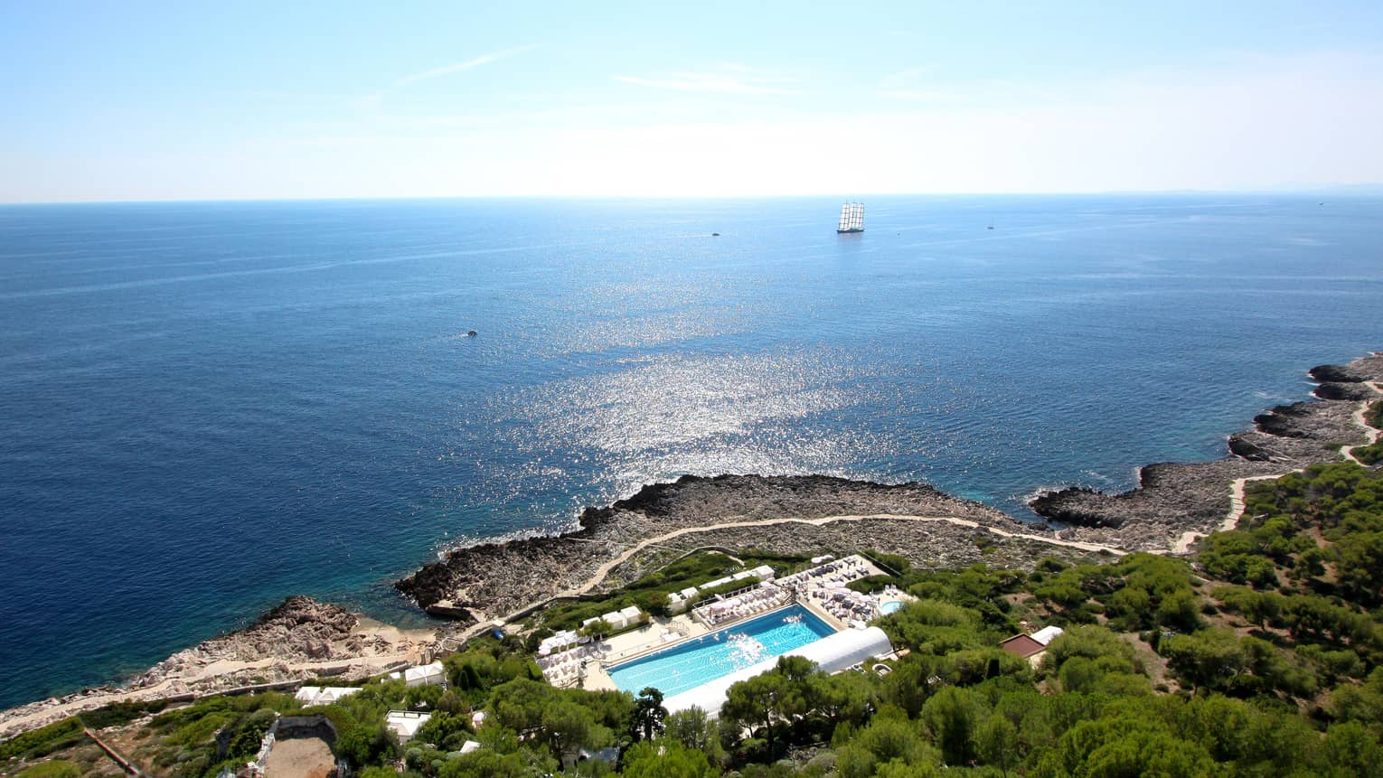 Aerial view of Four Seasons Cap Ferrat resort on lush mountain by sea