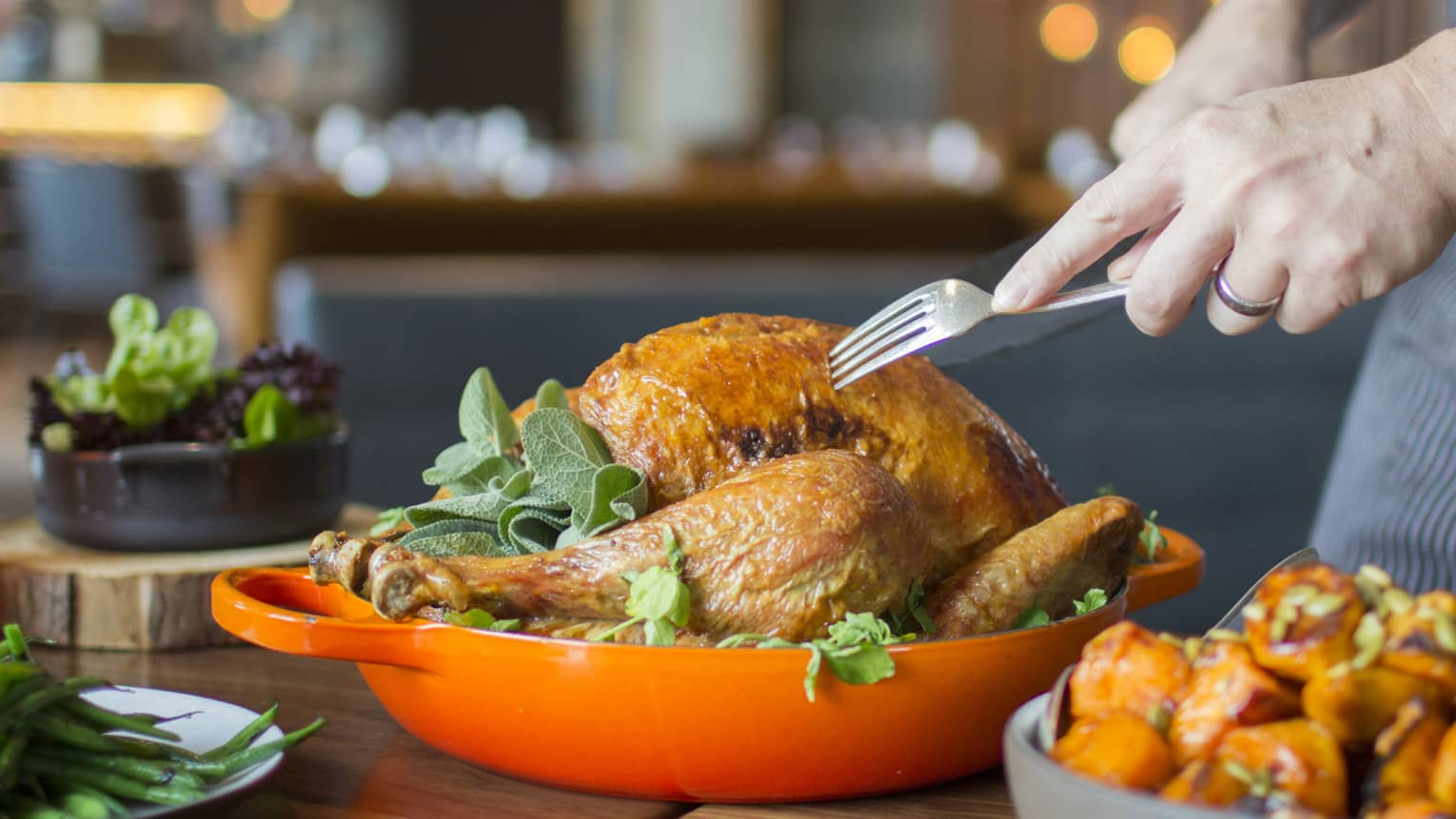 Thanksgiving turkey in orange dish being served by server holding fork