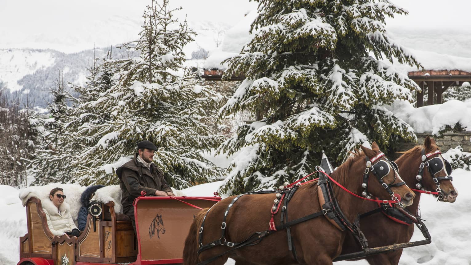 Guests explore a snow covered Megeve in a horse drawn carriage