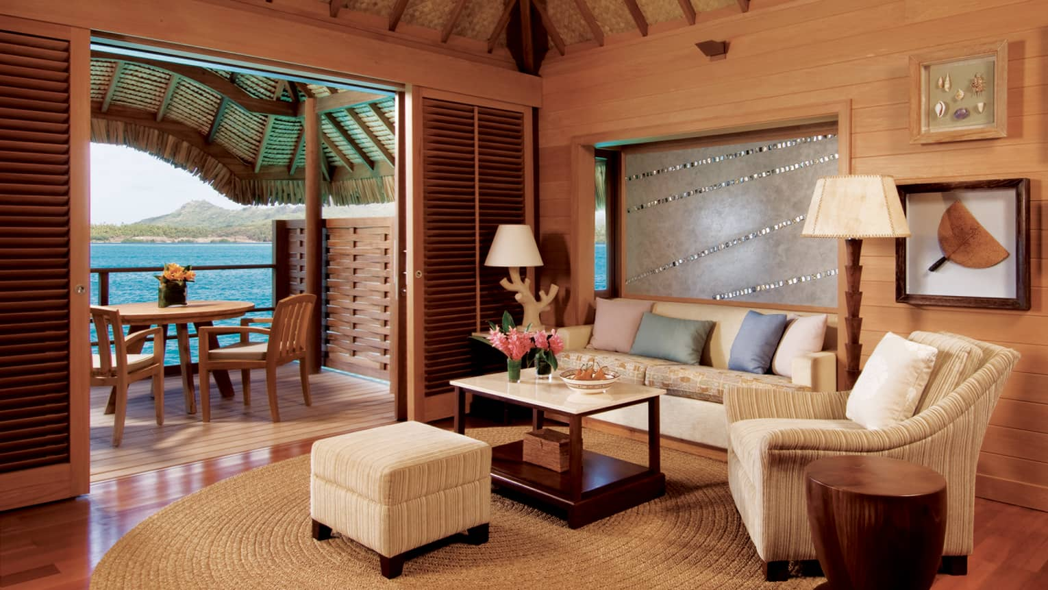 One-bedroom overwater suite living room with white sofa and chair, patio door with lagoon view