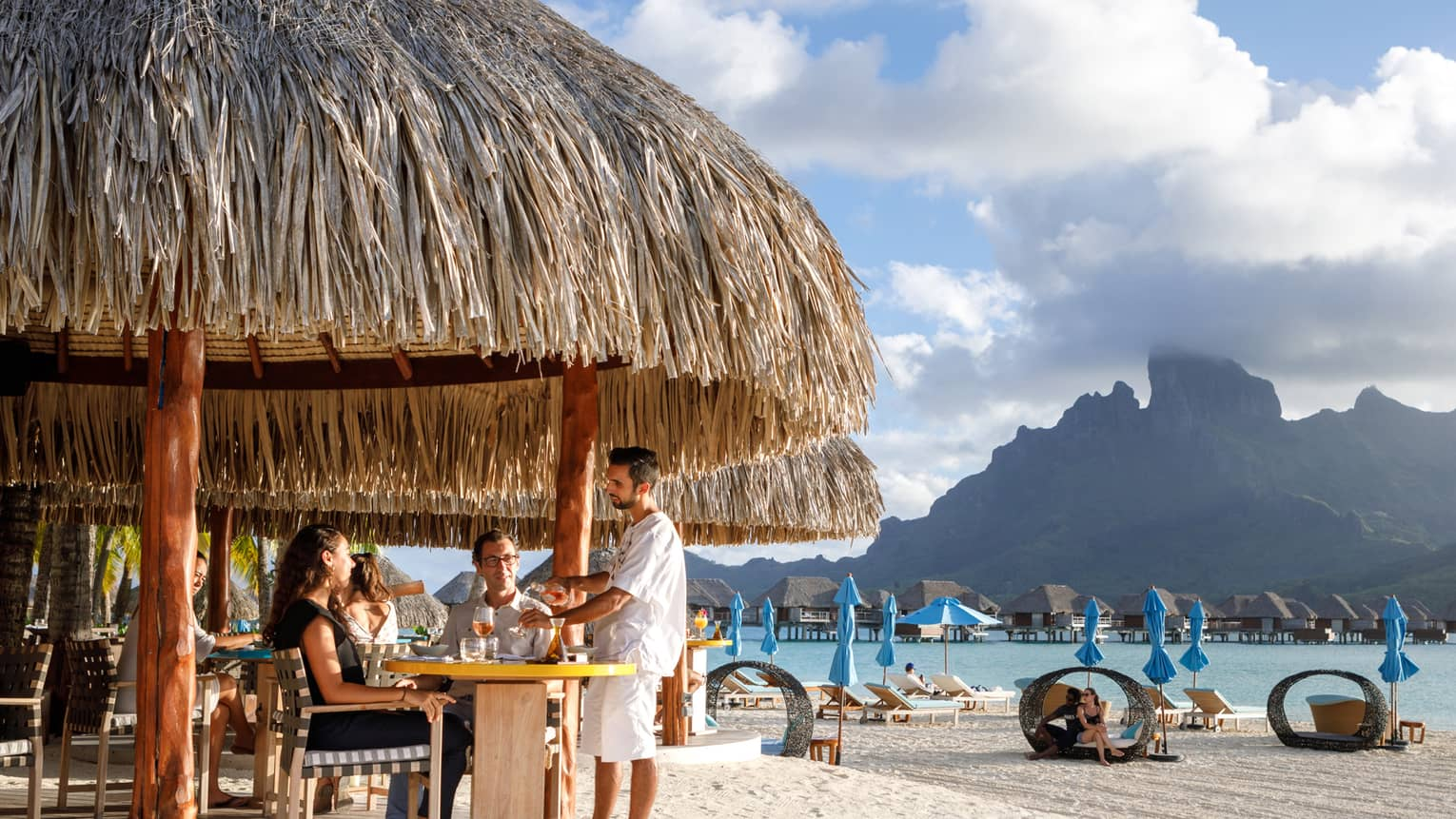 Couple seated in bar under grass roof on beach, view of people in personal cabanas, mountain view