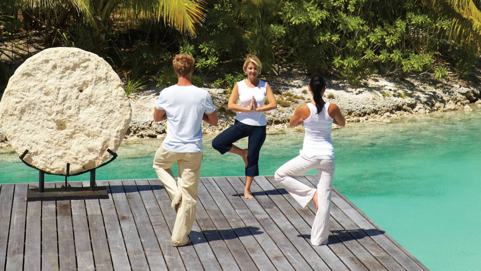 Man and two women in yoga poses on dock, standing on one leg with hands in prayer