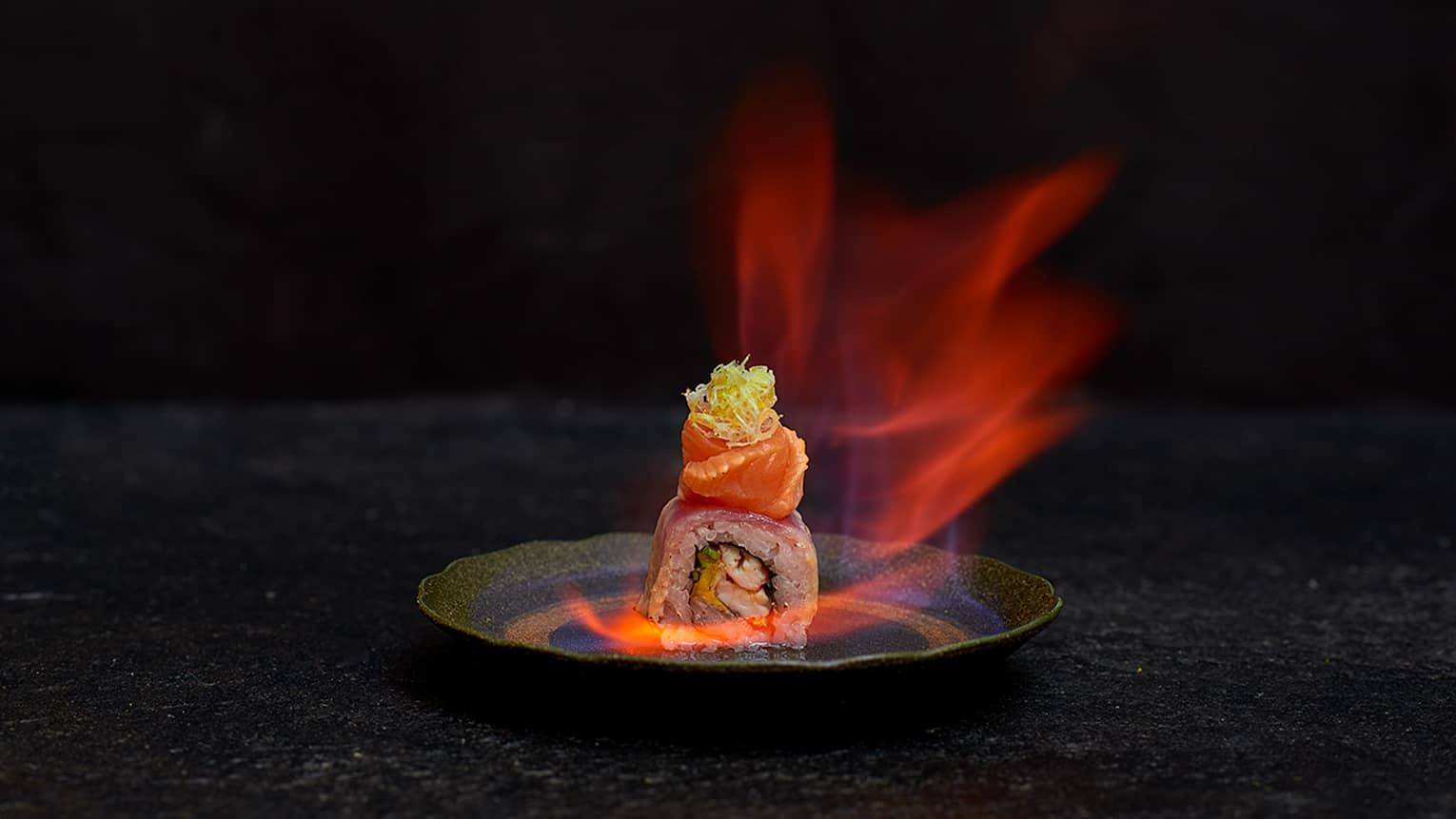 Flaming Sushi shrimp and rice roll topped with fresh salmon, engulfed in flames