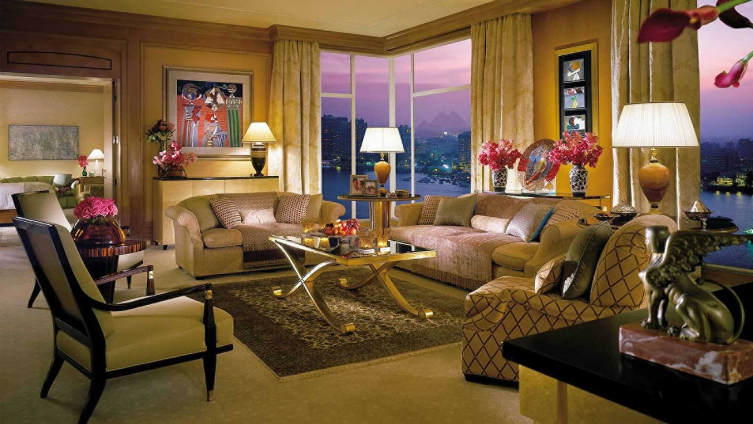 Royal Suite large living room at night, with two plush sofas and three armchairs, modern art and gold accents
