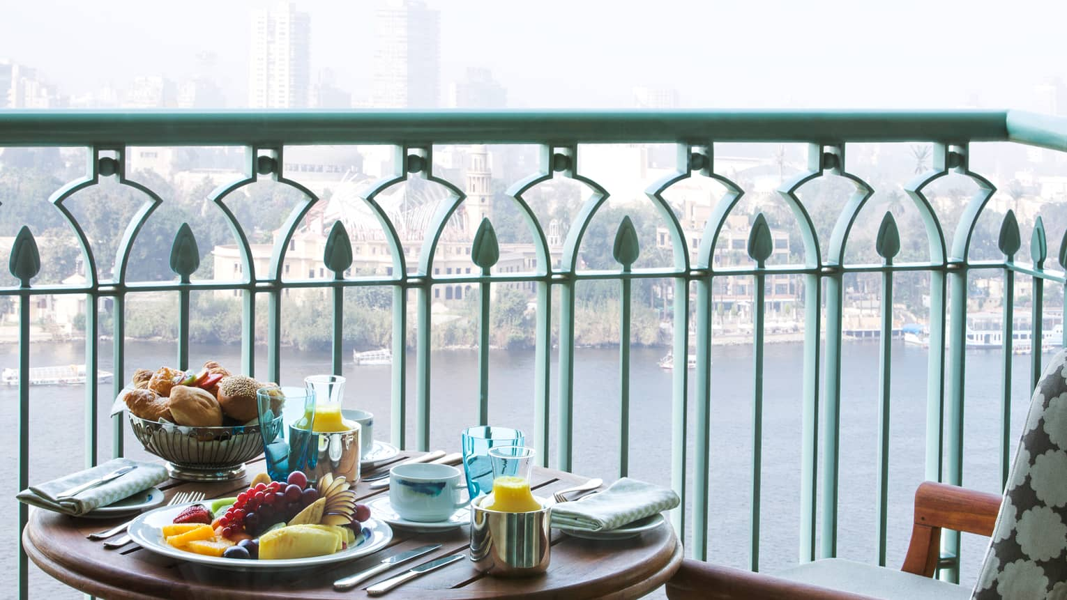 Close-up of patio breakfast table with fresh fruit, bread and juice, beside blue iron balcony overlooking river