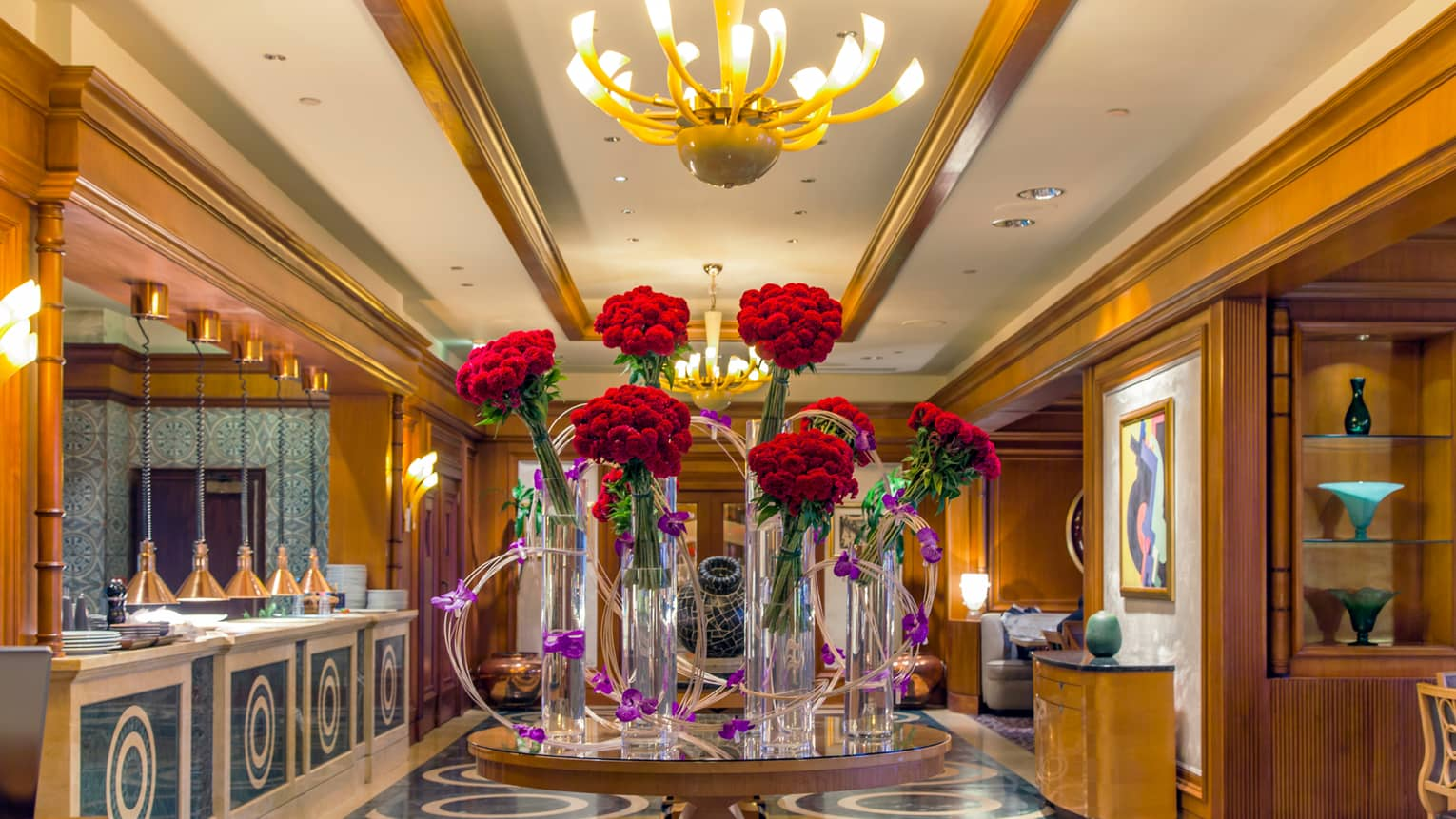 Bella Restaurant marble and wood hallway with table displaying six modern glass vases with red flowers