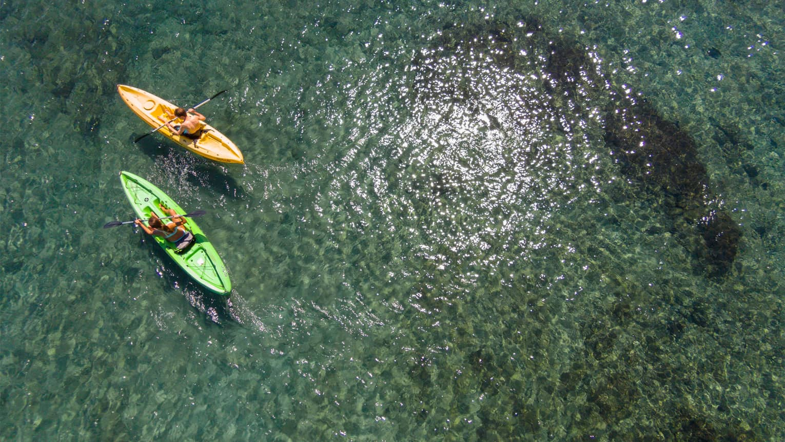Aerial view of man and woman in green and orange kayaks on reef