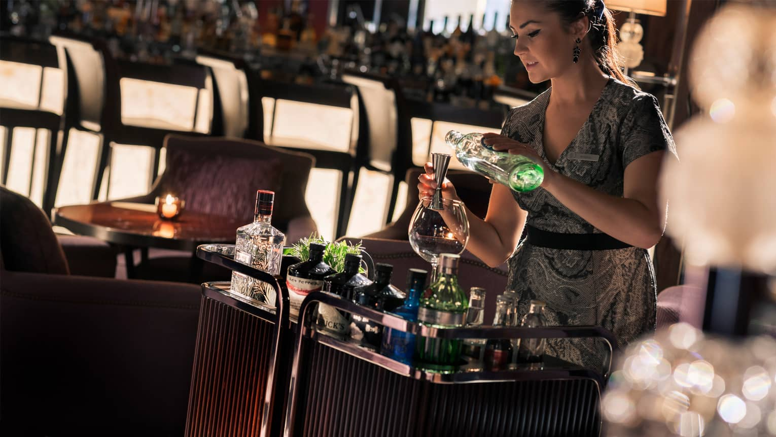 Hendricks Bar server in lounge with gin and tonic trolley pours liquor into shot glass