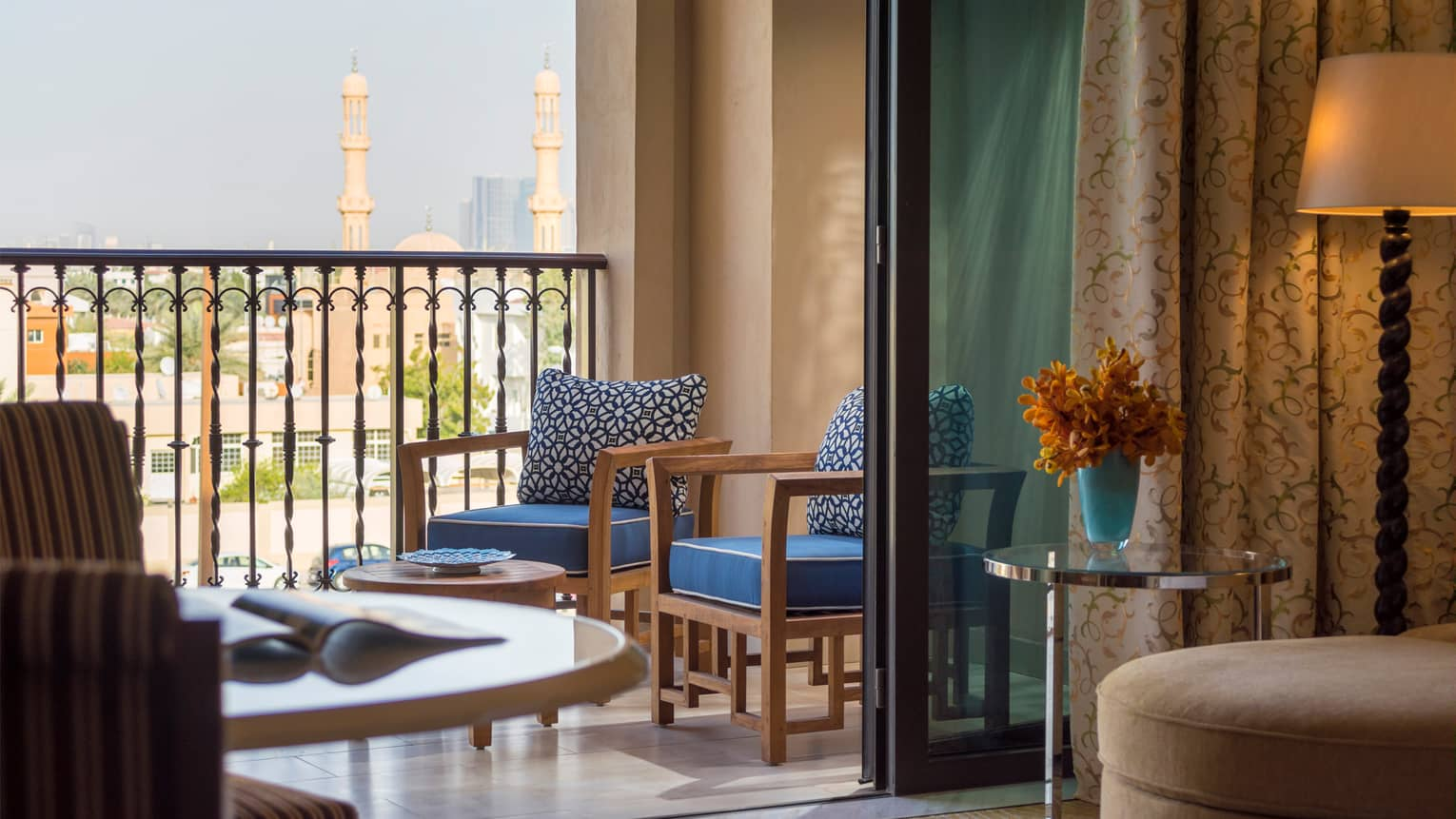 Deluxe City View room looking out at patio with two wood chairs and blue cushions, Dubai skyline views