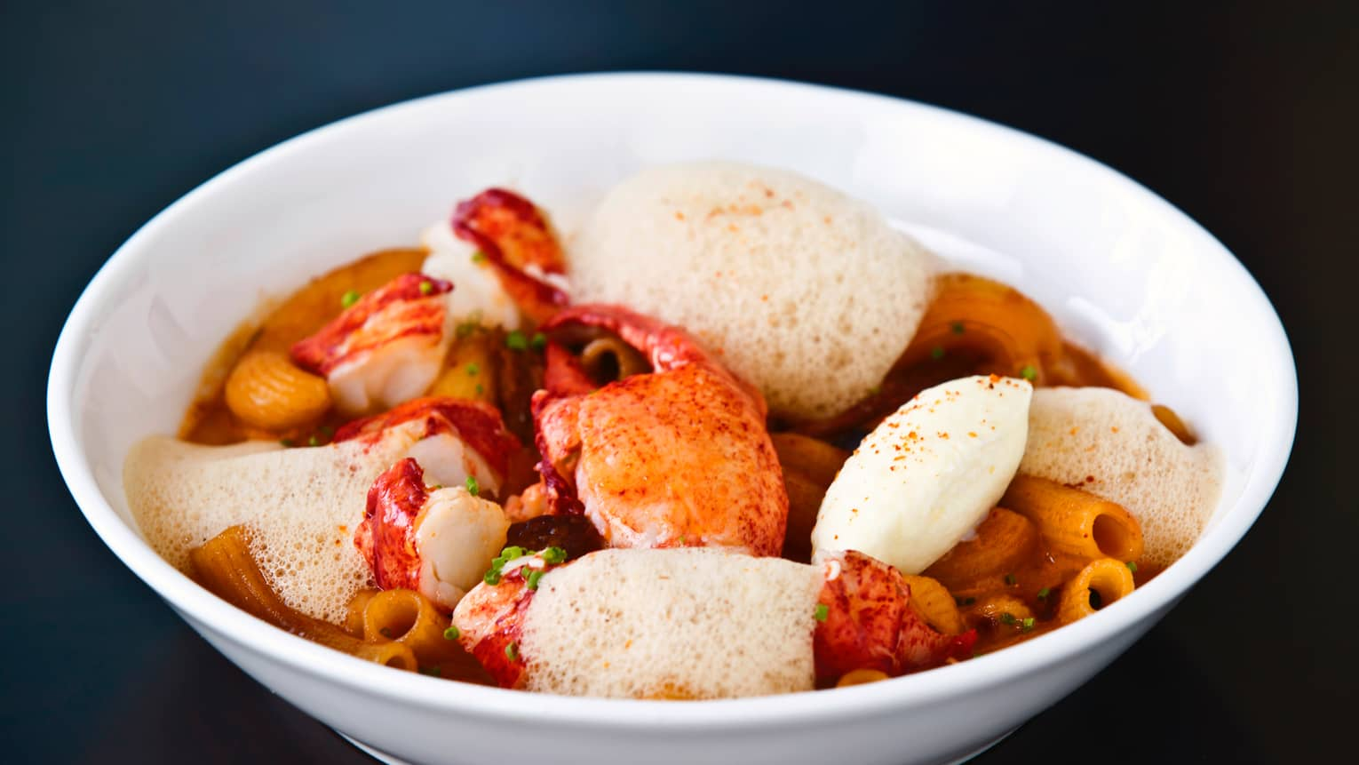 White bowl with lobster and fried wontons in lemongrass, creamy crustacean sauce and coconut foam