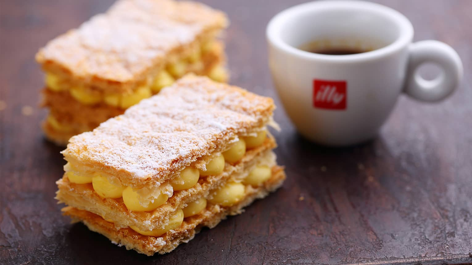 Two Millefoglie bars of crispy puff pastry and custard filling beside small Illy espresso mug