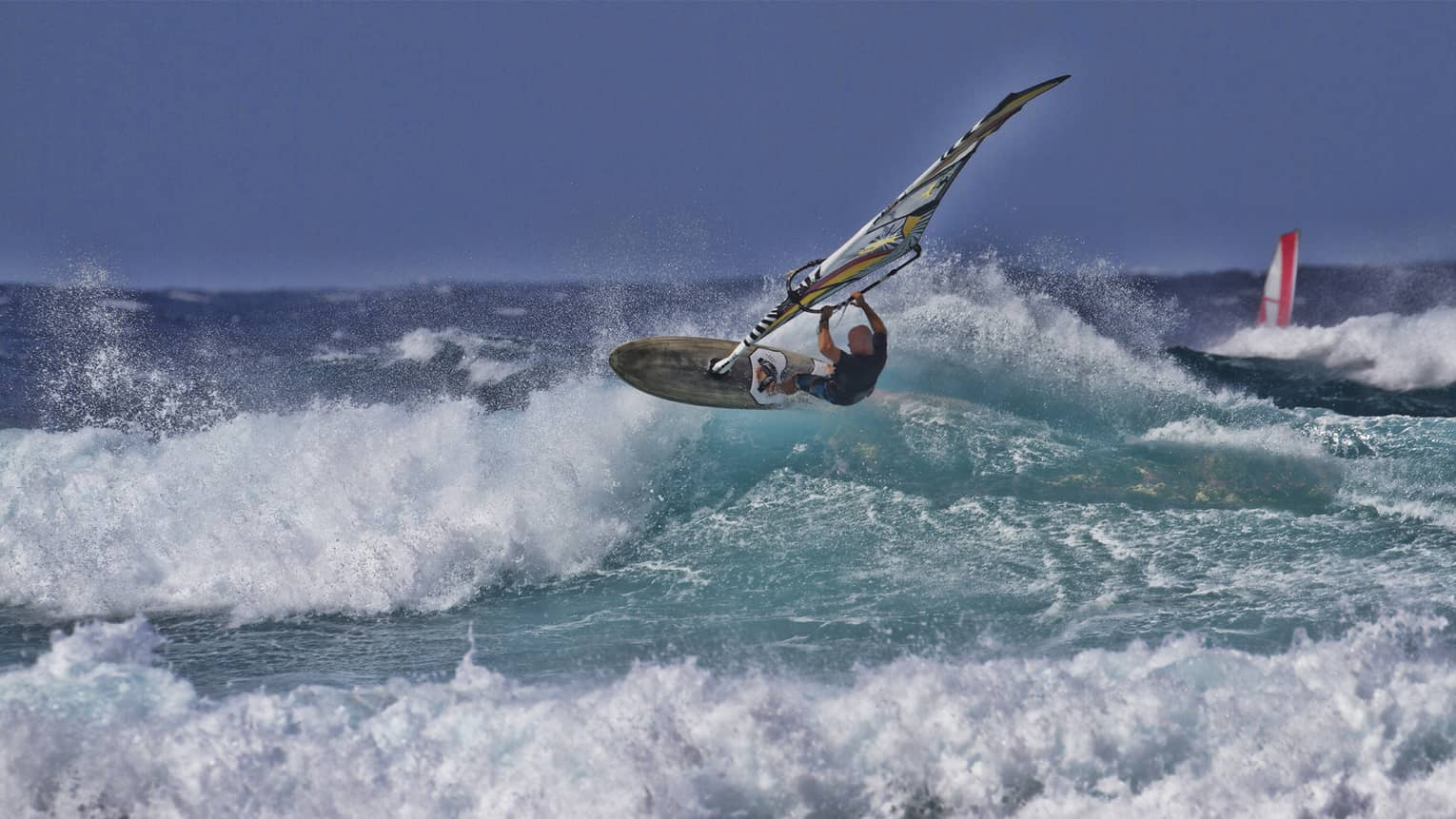 Man windsurfs over crashing wave on ocean