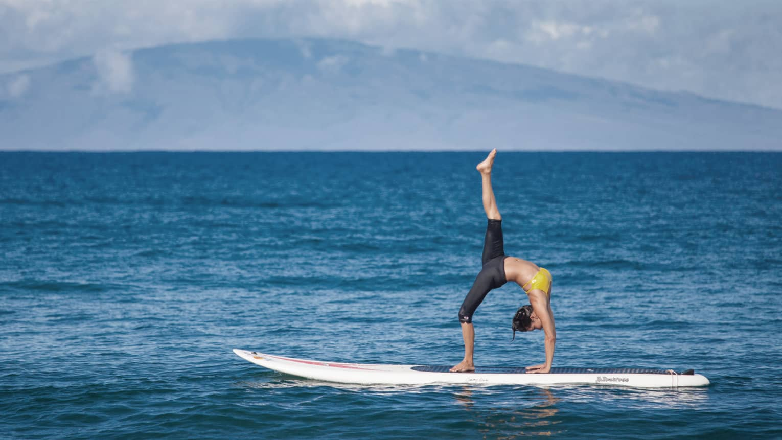Woman balances in upside-down yoga pose on paddleboard on ocean