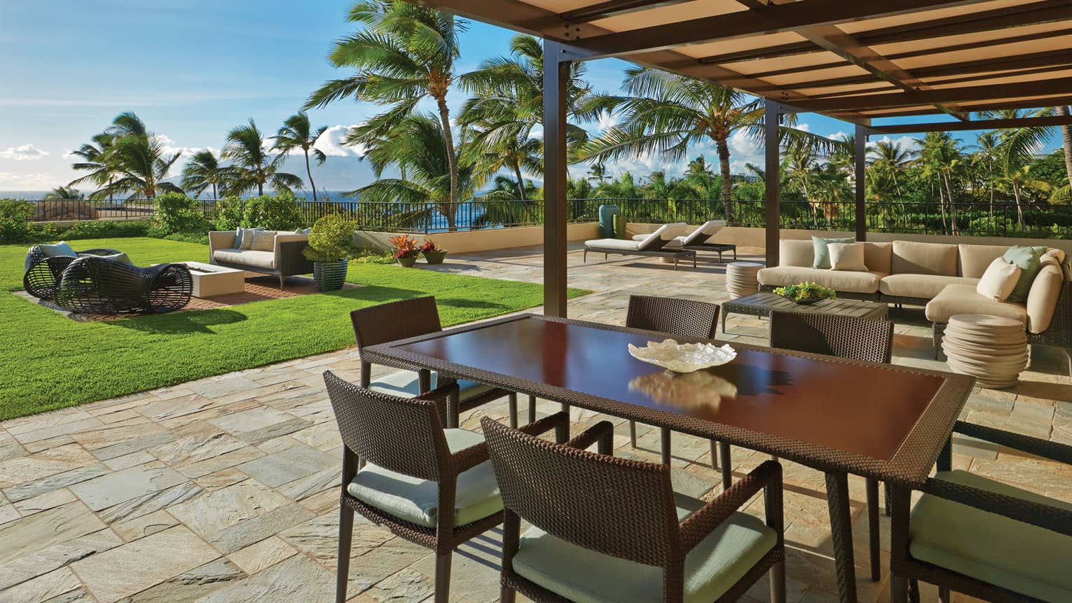 Lokelani Presidential Three-Bedroom Suite sunny outdoor patio with sofas and wicker dining table