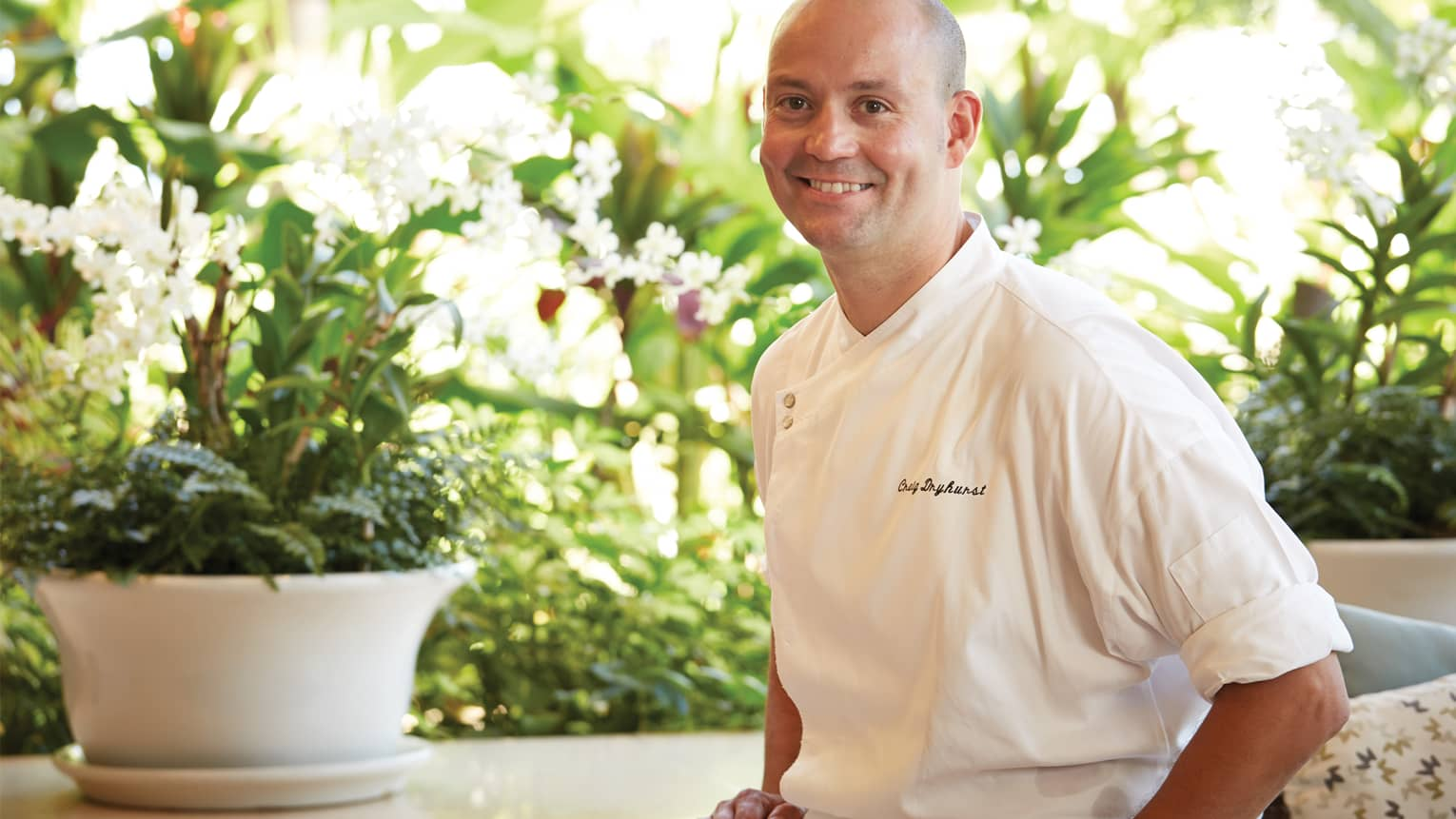 Portrait photo of Craig Dryhurst, Executive Chef on patio, white planter and flowers in background