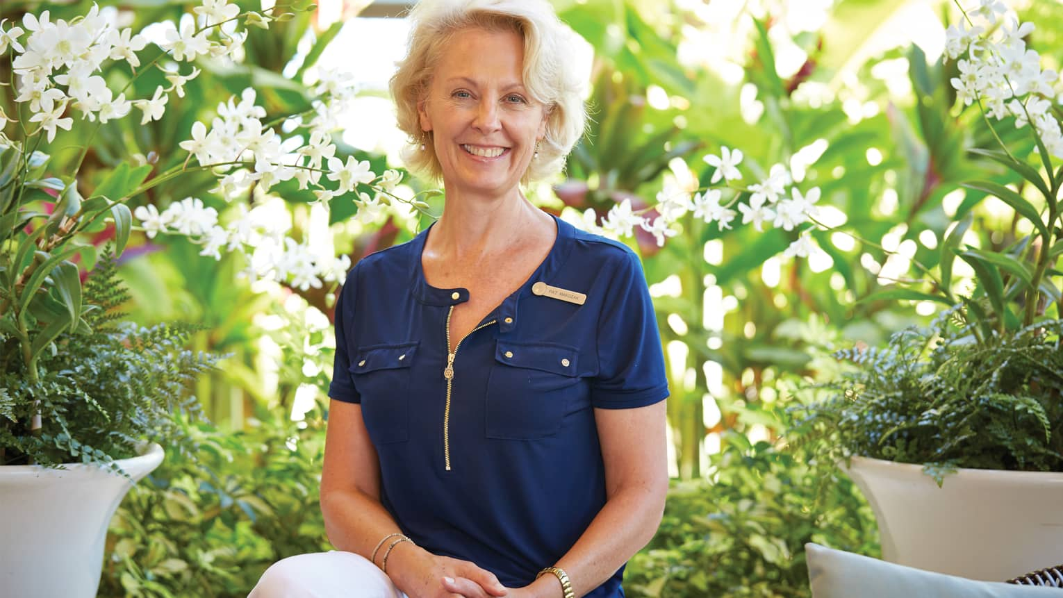 Portrait photo of Pat Makozak, Senior Spa Director between planters with tropical white flowers
