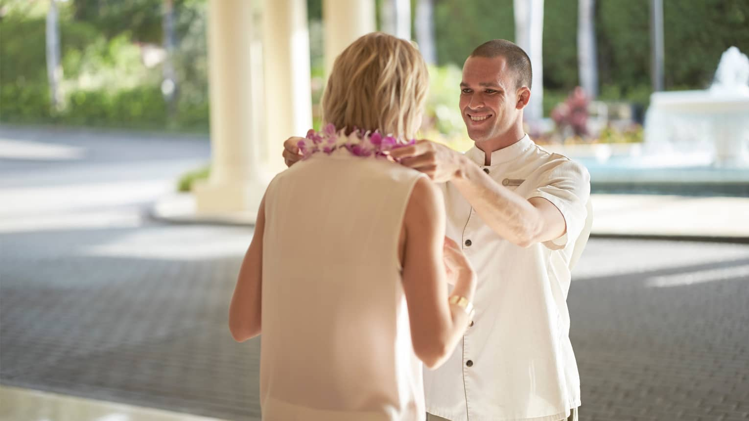Man in white hotel uniform puts purple Hawaiian lei garland around woman's neck