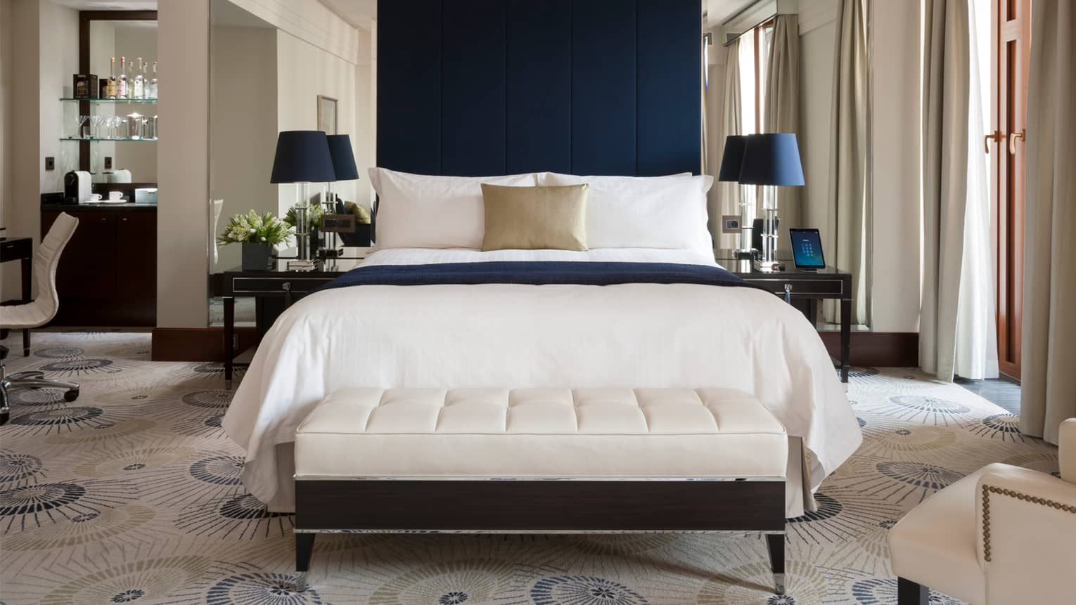Grand Premier Room white bed and plush bench, dark blue fabric headboard, iPad on nightstand
