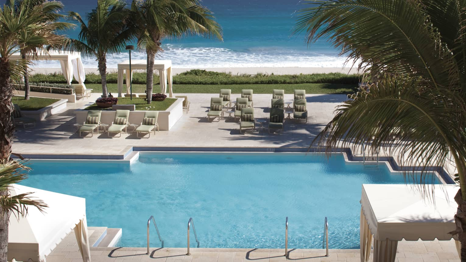Heated outdoor pool surrounded by palm trees, white cabanas and lounge chairs, ocean in view