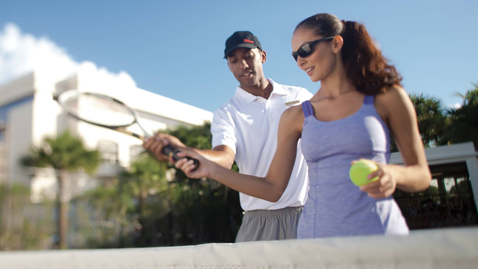 Woman in blue dress holds tennis ball and racket as tennis coach stands behind, assisting with swing
