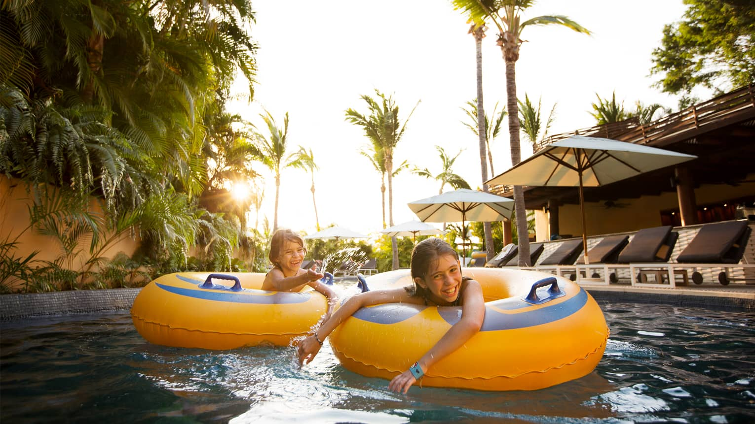 Two children smile in yellow inflatable tubes on lazy river, palms and pool deck in background