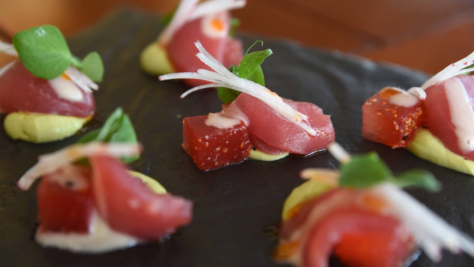 Small watermelon cubes with sashimi arranged on dish, garnished with crispy white radish, mint