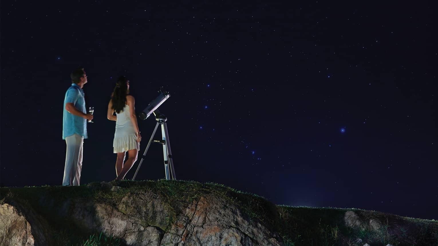 Woman in white dress and man in blue, holding wine glass stand by telescope looking up at stars