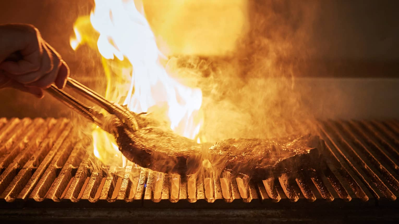 Fiery barbecue with silhouette of hand holding tongs, flipping large steak on grill