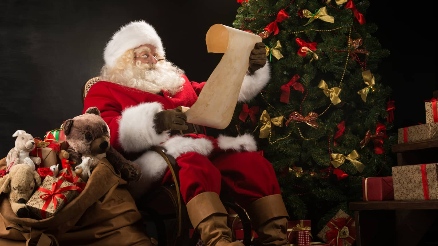 Santa Claus seated in large rocker holding a scroll, flanked by decorated Christmas tree with gifts and overflowing gift bag