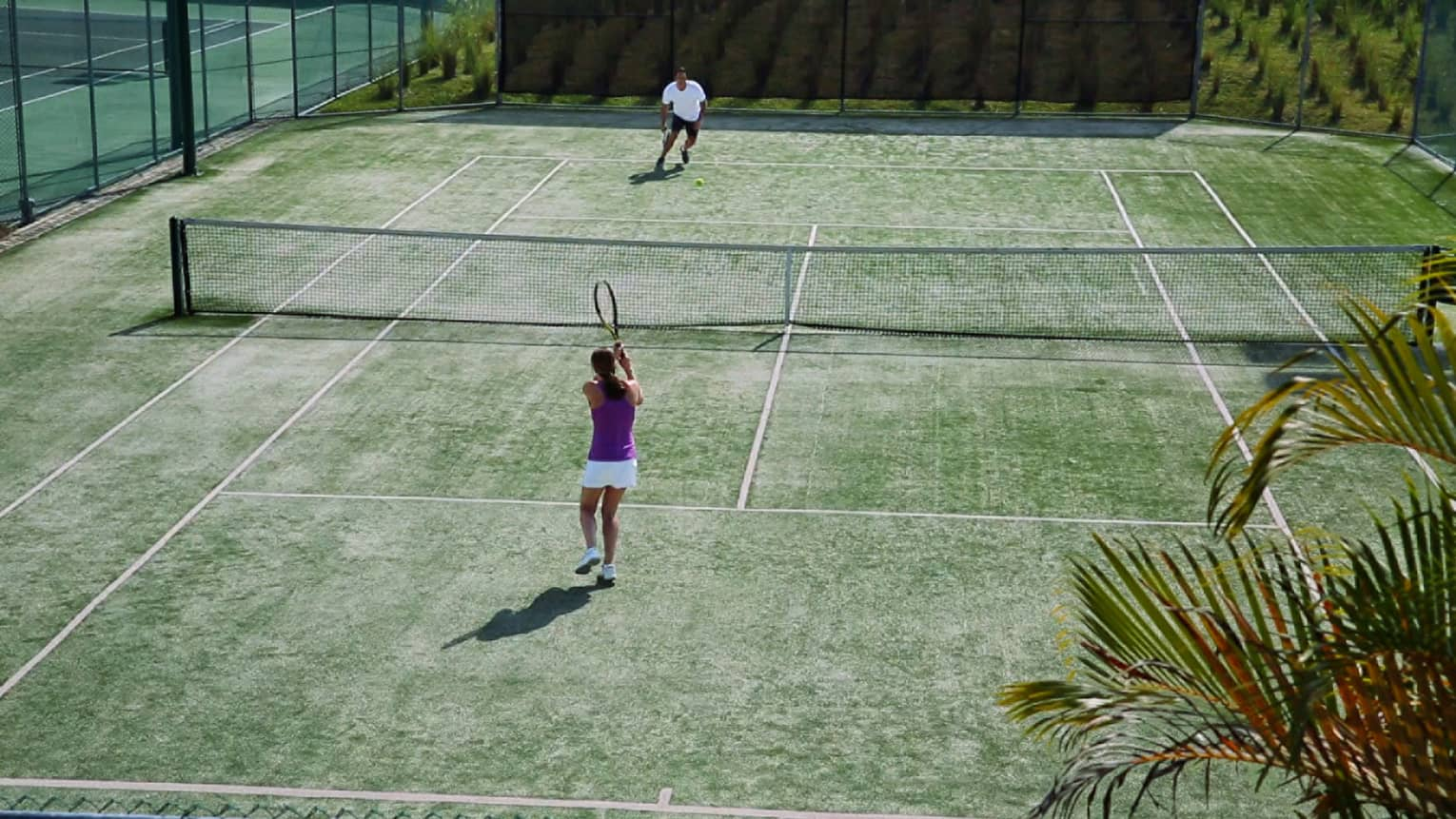 Aerial view of woman with tennis racket serving ball over net to man on court
