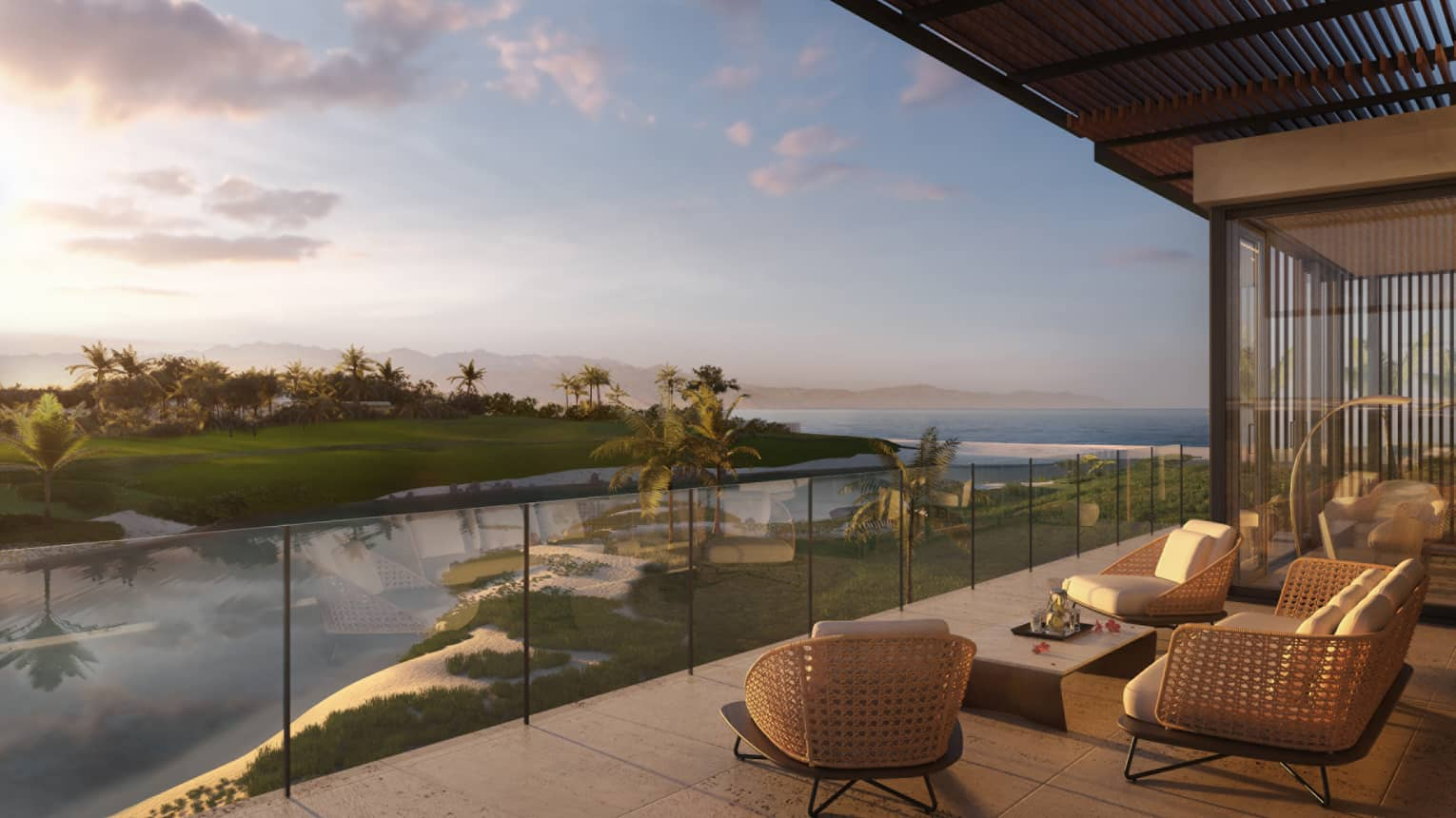 Modern wicker patio furniture by glass balcony overlooking water, green lawns at sunset