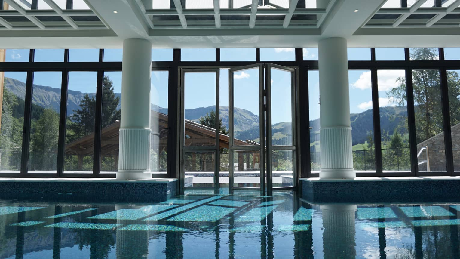 Large white pillars, beams, skylights over indoor swimming pool