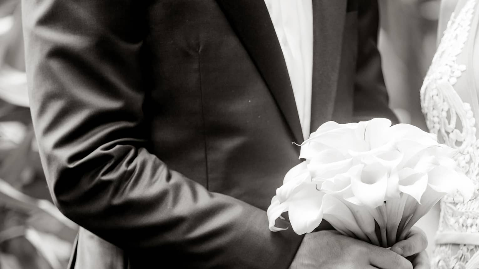 Black and white image of bride wearing lace dress, groom holding wedding bouquet