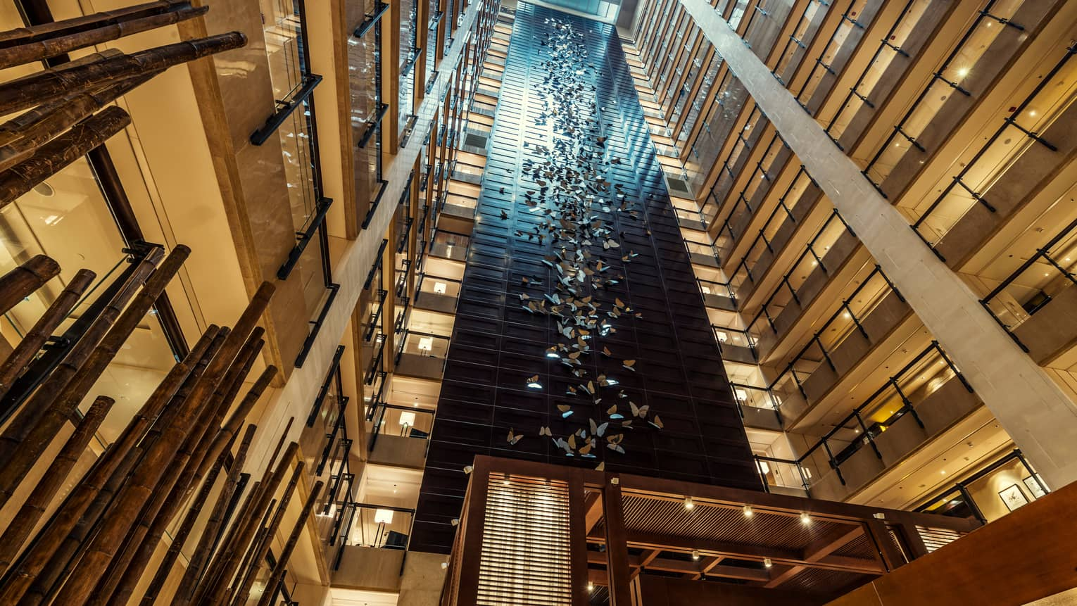 Looking up in 20-storey hotel atrium at 400 stainless-steel butterflies on column
