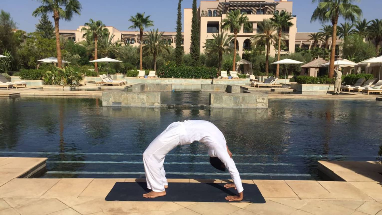 Person wearing white poses in arched yoga bridge pose beside outdoor swimming pool
