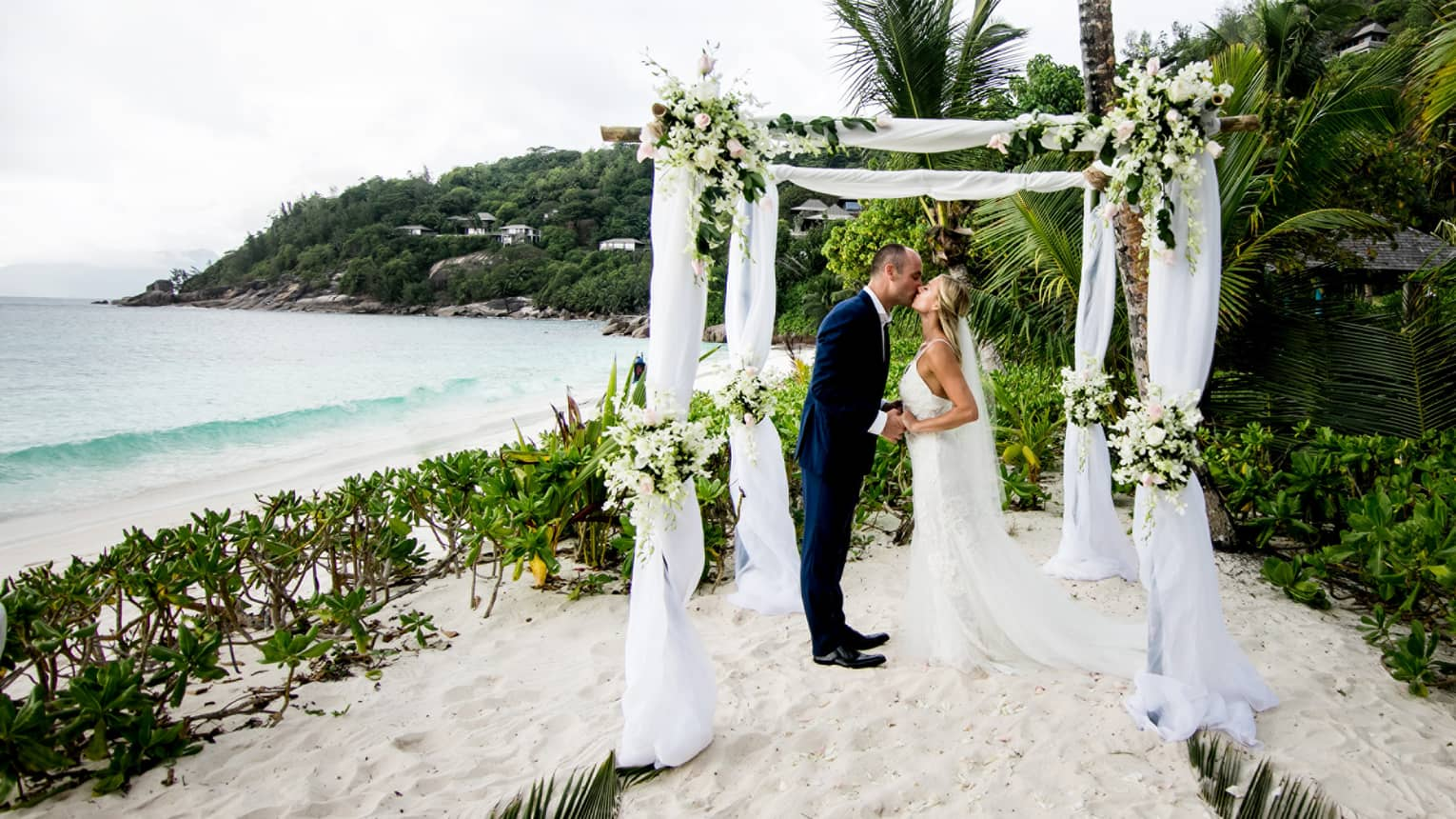 Wedding couple kissing under decorated canopy standing on sand surrounded by greenery and ocean