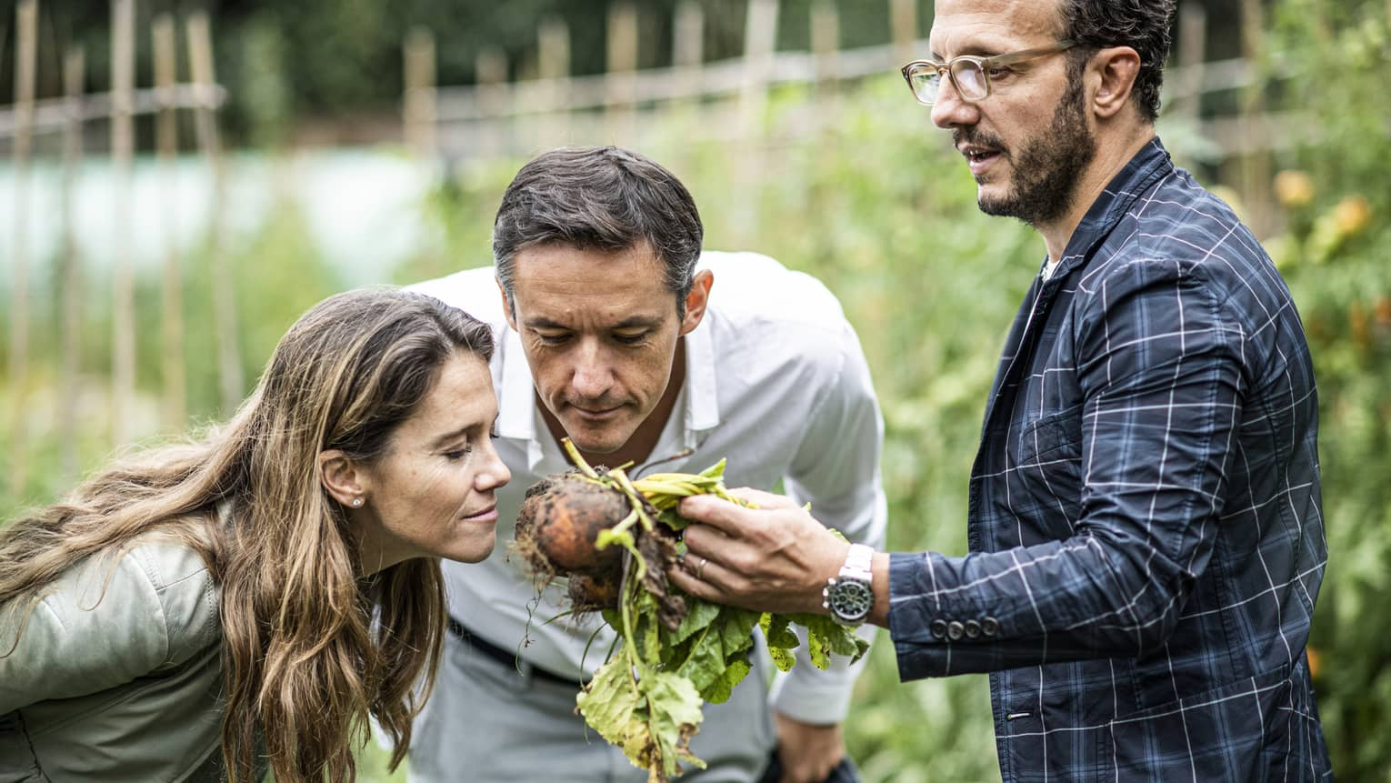 A man and woman lean in to smell a root vegetable in the garden