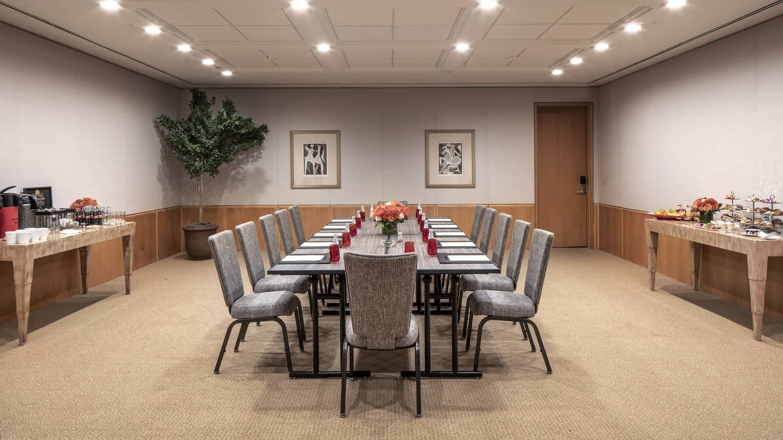 A boardroom with a long rectangular gray table that is set with red water glasses, a black folder, white paper and a orange floral centerpiece.