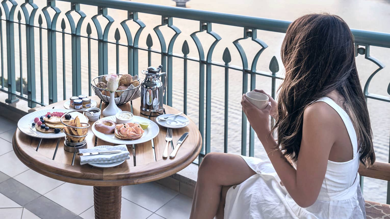 Dark-haired woman in white dress seated at balcony bistro table looking through railing at river and city views