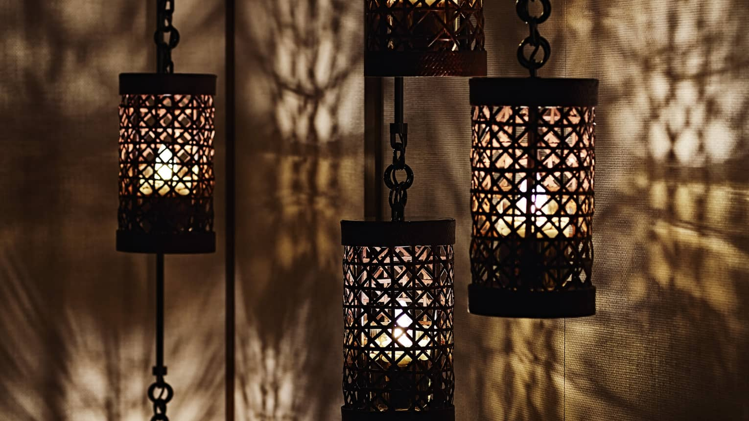 Close-up of black lanterns hanging from chains, light reflected on walls