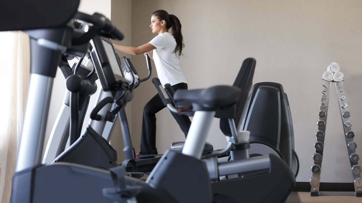 Woman in white shirt, black pants works out on cardio elliptical machine in sunny Fitness Centre