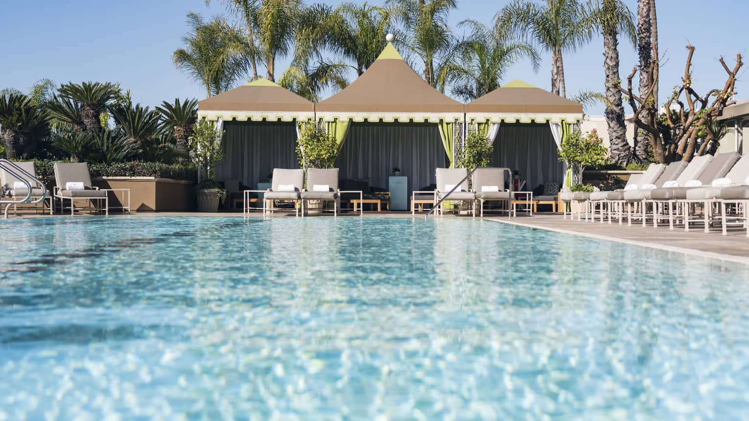 Lounge chairs, cabanas around large outdoor swimming pool under sunny sky