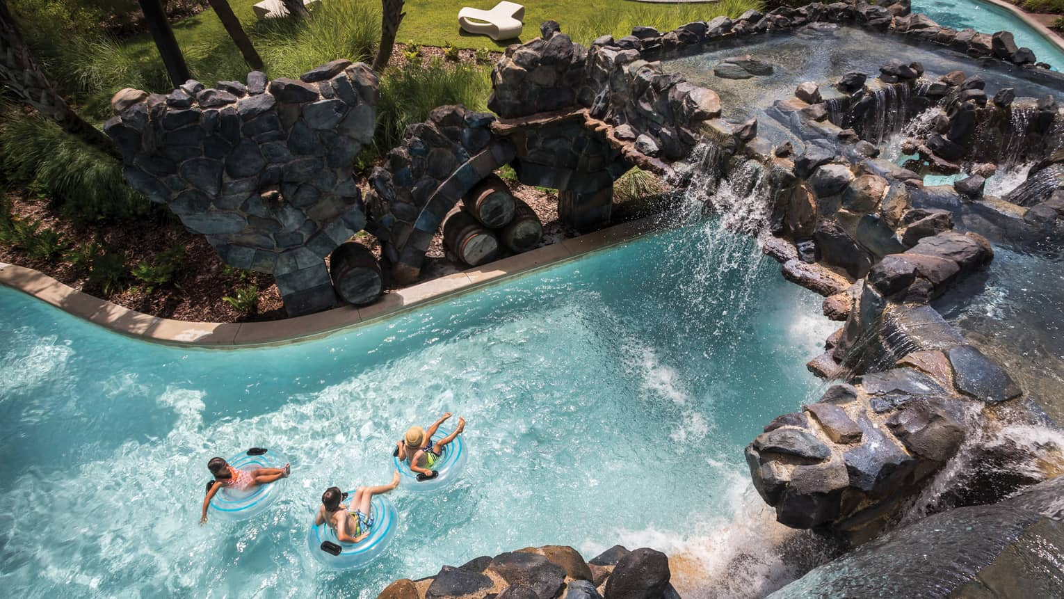 A bird's-eye view of three people floating in inner tubes down a rock-lined lazy river pool at four seasons resort orlando at Walt Disney World