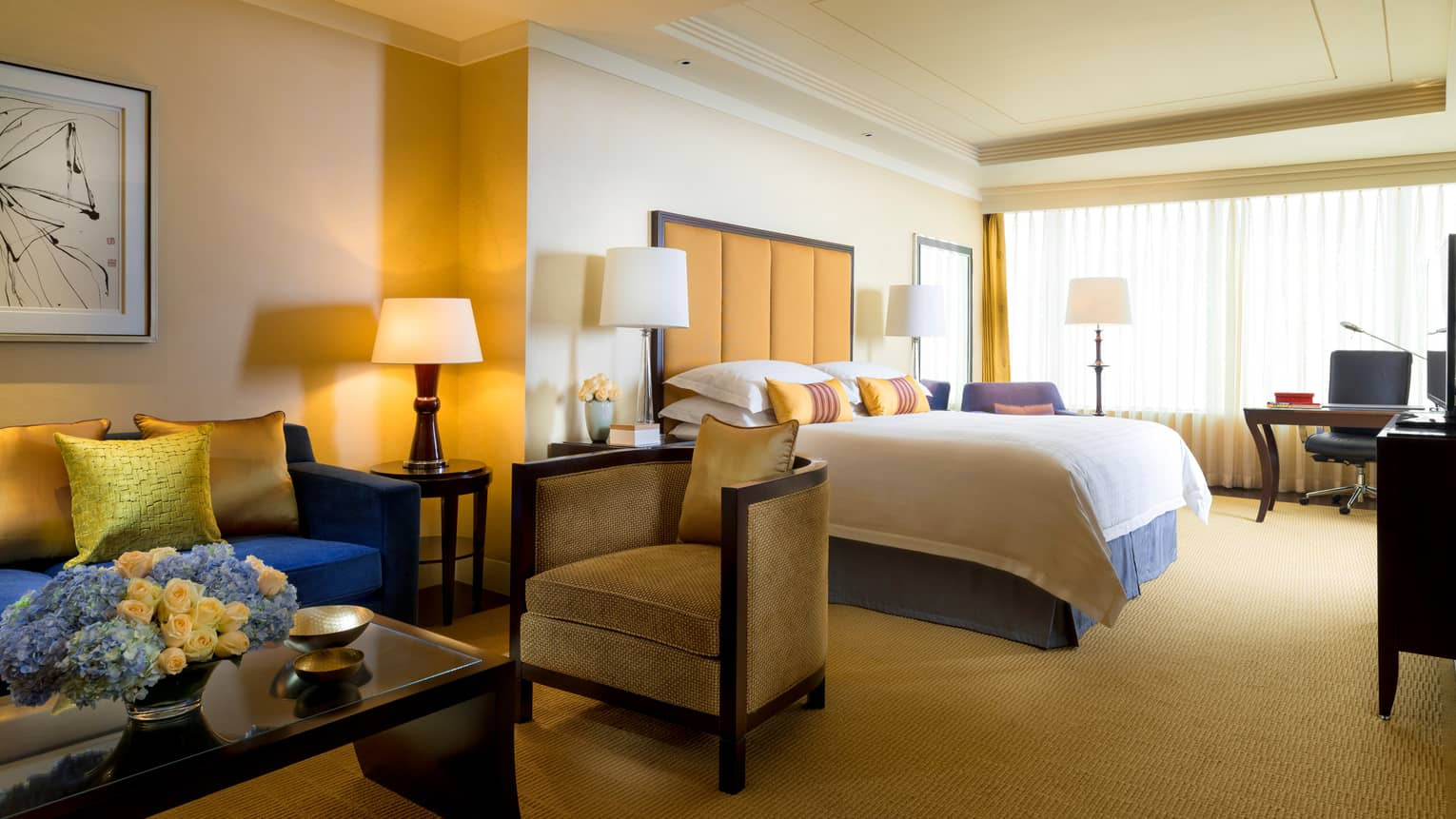 Four Seasons Room sitting area with coffee table, small armchairs beside hotel bed