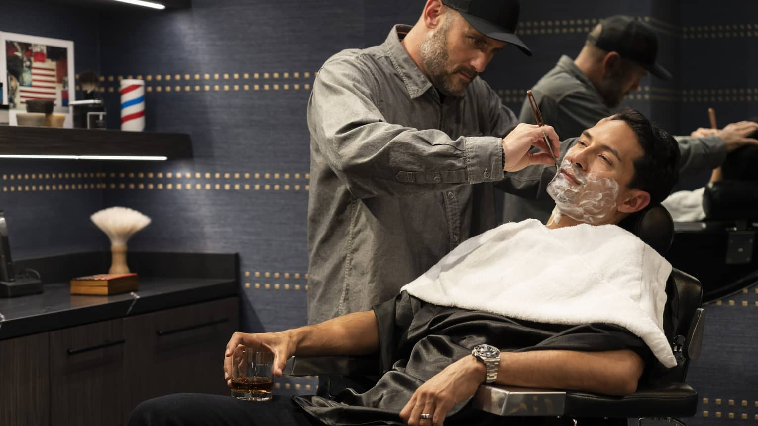 Aman reclines in a barber chair while a barber shaves his beard with a straight razor