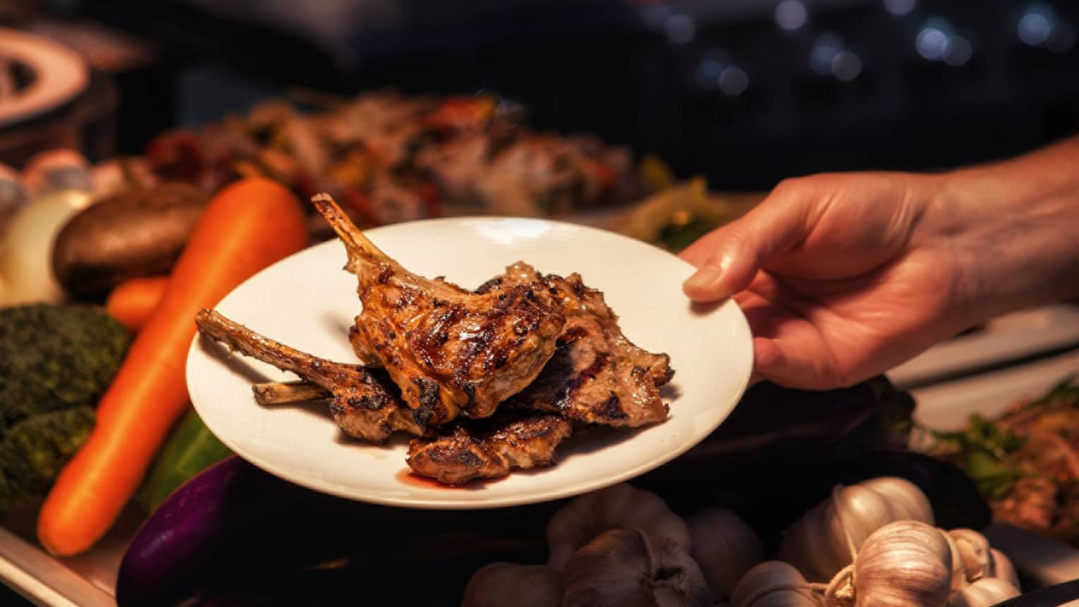 Hand holding barbecued chops on plate over fresh vegetables