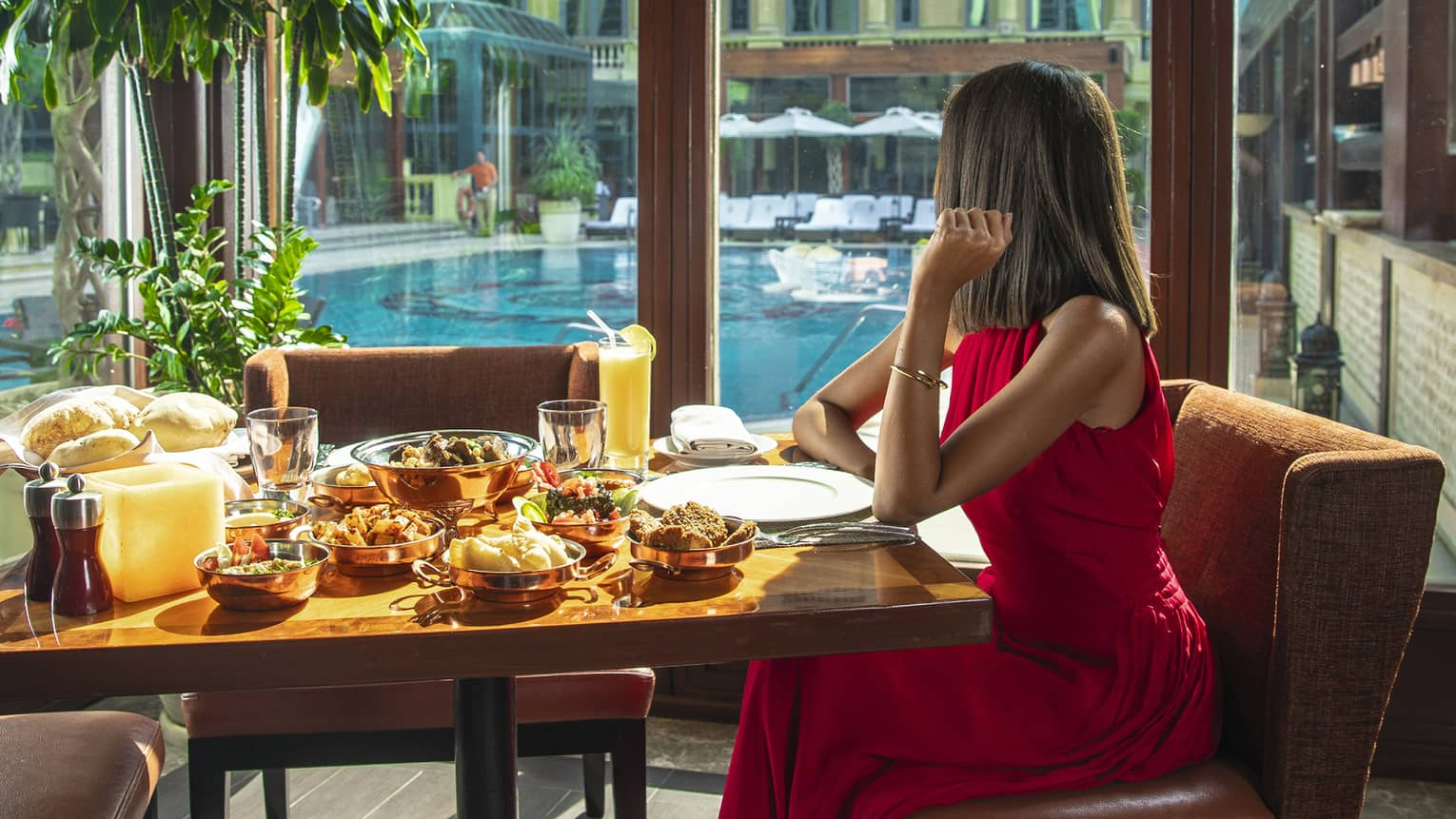 A woman in a long red dress sits at a table with a variety of food next to a long window overlooking a pool