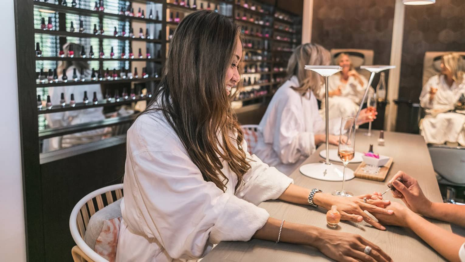 Women in white bathrobes sit at table, get manicures at Driftwood Spa